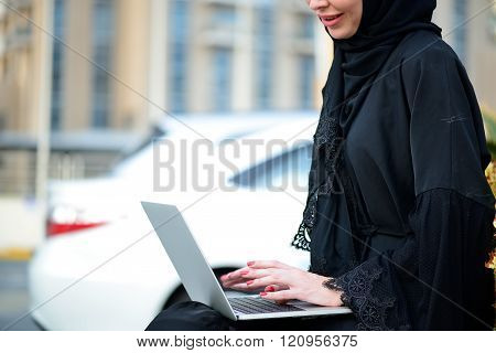Emarati Arab Business woman using laptop in Dubai, United Arab Emirates.