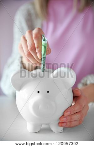 Woman putting euro banknote into white piggy bank at the table