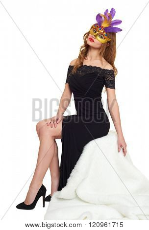 Young woman in black evening gown and carnival mask. Sit on white fur. Holiday and party concept.