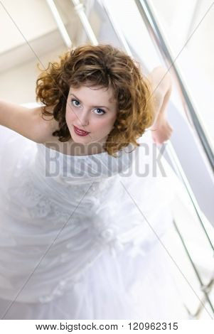 The Bride In A Wedding Dress Going Down The Stairs And Looking Up