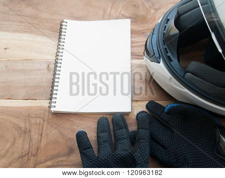 Black Gloves Motorcycle And White Helmet And White Book On Wood Table
