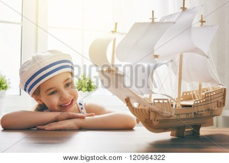 Adorable little child girl looks at toy ship and dreams of sea, adventures and travel.