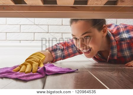 Beautiful young woman makes cleaning the house. Girl rubs dust.