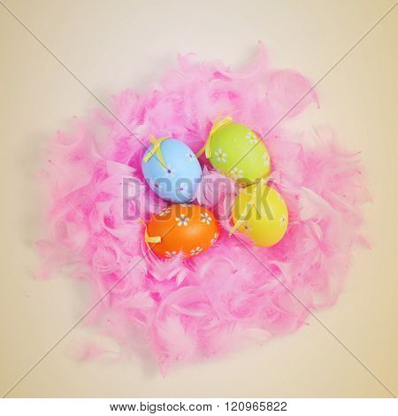 high-angle shot of some decorated easter eggs of different colors in a nest made with pink feathers, on a beige background