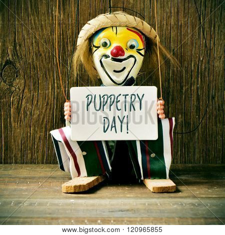 closeup of an old marionette with its face painted as a clown holding a signboard with the text puppetry day