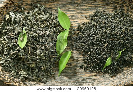 Dry tea in plate with green leaves, closeup