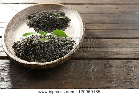 Dry tea in plate with green leaves on wooden table background