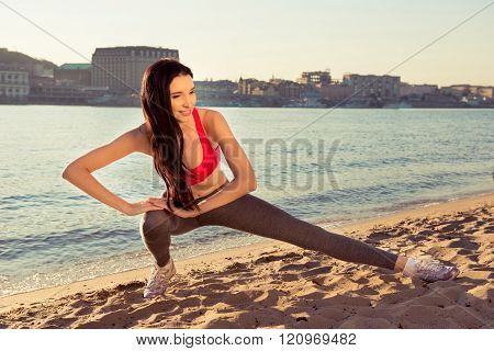 Young Fit Sportswoman Stretching Near The Sea