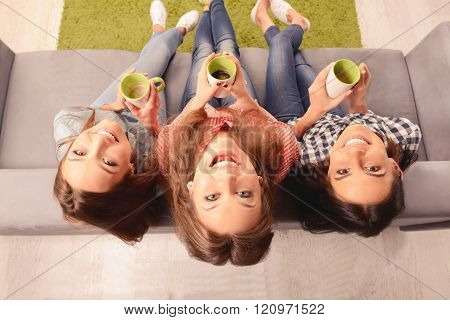 Top View Photo Of Cheerful Girls Sitting On Couch With Cups
