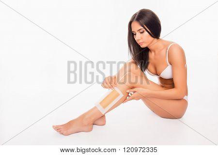 Beautiful Young Woman  Shaving Her Leg With Wax Stripe