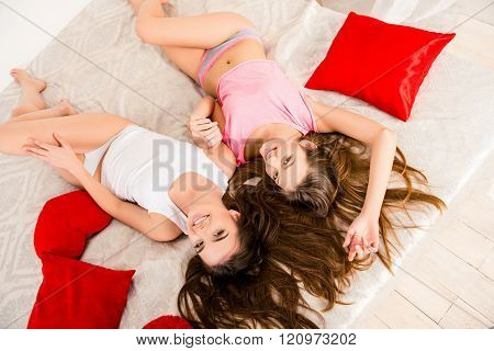 Top View Photo Of Two Sexy Girls Lying On Bed And Holding Hands