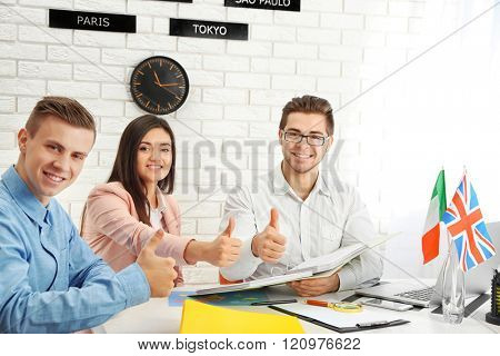 Agent and happy young couple in the office of travel company