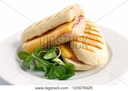 Cut cheese and ham toasted panini melt. On white plate with garnish.
