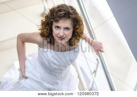 The Bride With Curly Hair In A Wedding Dress Going Down The Stairs And Looking Up