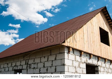 House Of The Blocks With Roof Of Tiles And Wooden Loft Under A Blue Sky