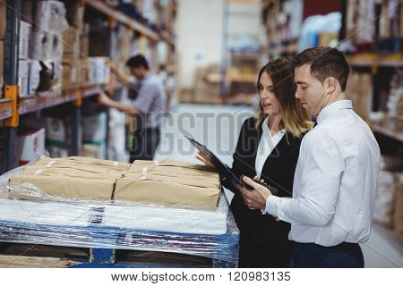 Warehouse managers looking at clipboard in warehouse