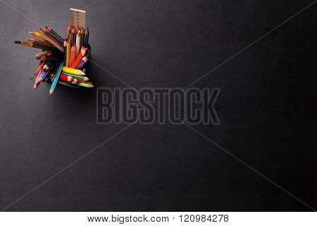 Office leather desk table with colorful pencils. Top view with copy space
