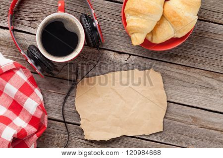 Fresh croissants and coffee on wooden table. Top view with paper for copy space