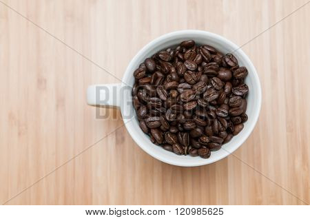 Strong flavored coffee beans in a plain white mug