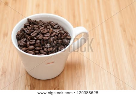 Strong flavoured coffee beans in a plain white mug