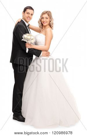 Full length portrait of a newlywed couple dancing together and looking at the camera isolated on white background