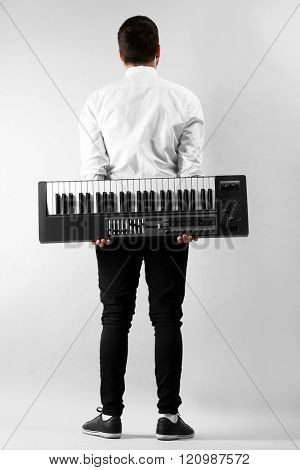 Man with synthesizer on light wall background