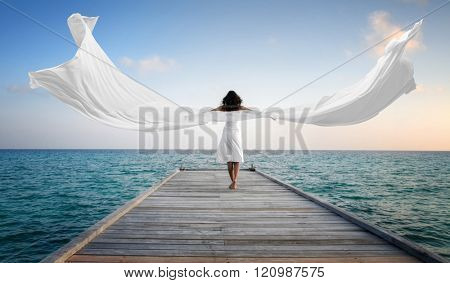 Sexy happy female model with white clothes standing on a jetty (