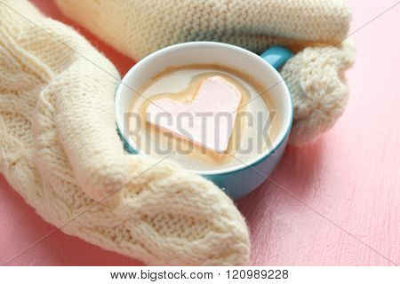 Female hands in warm mittens holding cup of hot cappuccino with heart marshmallow on pink background, close up
