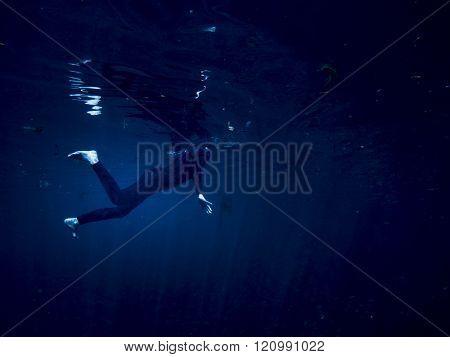Underwater shot of woman swimming alone in the dark, concept shot