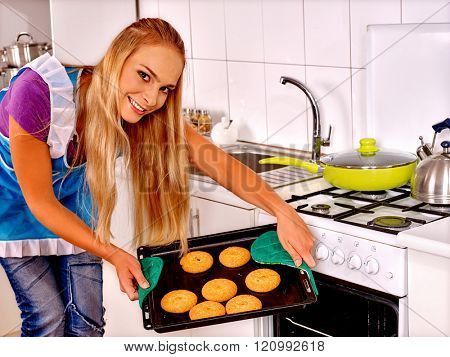 Young blond smiling woman is baking cookies at kitchen.