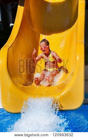 Happy girl kid on yellow water slide at aquapark. Summer holiday.