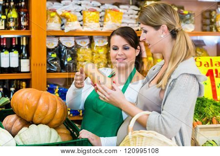 Woman buying pumpkin and vegetables in delicatessen