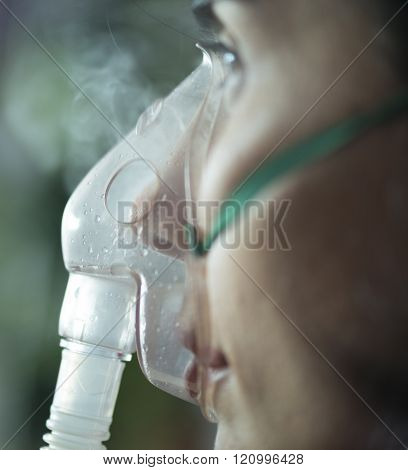 Close Up View Of A Woman  Using Nebuliser Mask