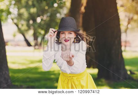 Sexual woman in hat, beckoning gesture, outdoors.