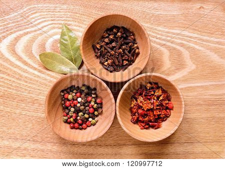 Three wooden bowls with pepper, cloves and slices of dried peppers on a light wooden table. Next to the bowl are two of dried bay leaves.