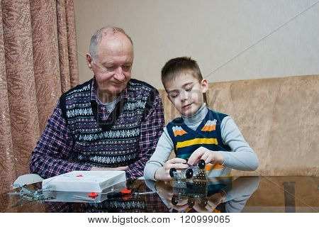 Grand-dad With A Grandchild Play A Designer
