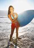 Vollansicht Portrait of Woman holding Surfbrett am Strand