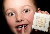image of child missing  - Boy with a missing tooth and excited to be receiving a visit from the tooth fairy - JPG