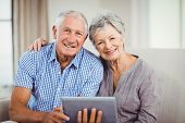Portrait of senior couple holding digital tablet and smiling while sitting on sofa in living room poster