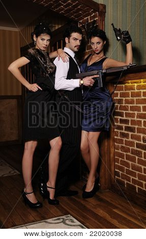 A guy and two beautiful young women in the image of gangsters with guns.