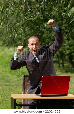 man with red laptop working outdoors, feels happy