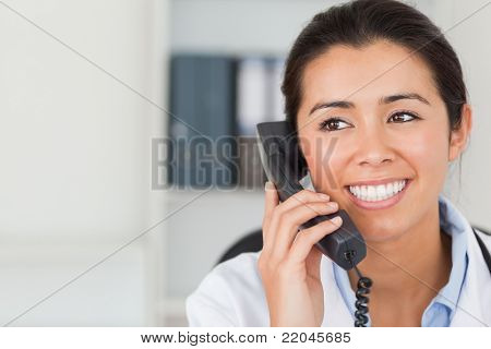 Good looking female doctor on the phone and posing in her office
