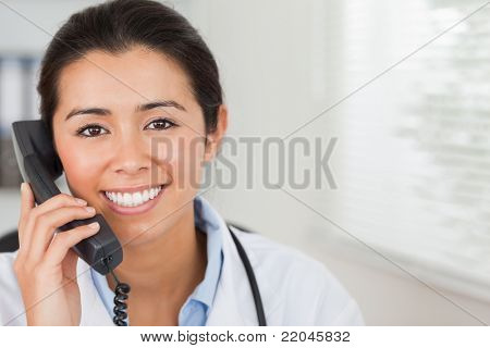Lovely female doctor on the phone and posing in her office