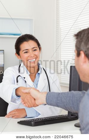 Attractive female doctor shaking a patient's hands in her office