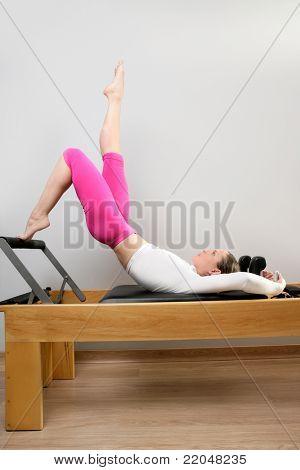 pilates teacher woman in reformer device doing legs exercise