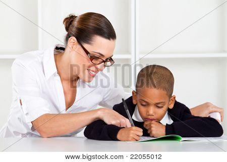 caring elementary teacher helping schoolboy