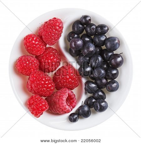 Red Raspberry Versus Black Bilberry In Yang Yin Shaped Plate, Isolated On White