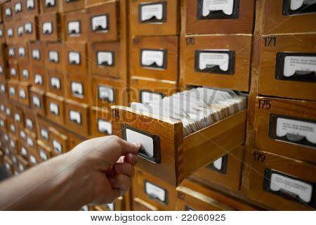 database concept. vintage cabinet. human hand opens library card or file catalog box.