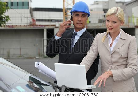 Architect and assistant stood by car with plan