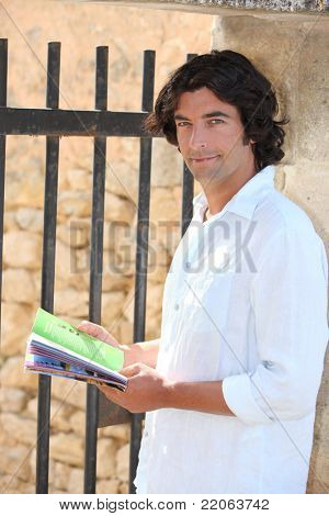 Male sightseer consulting a brochure